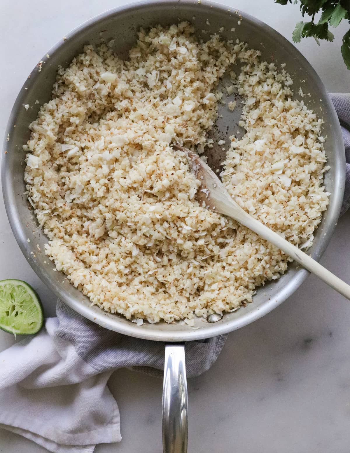 Top down of the cooked cauliflower rice in a skillet with a wooden spoon.