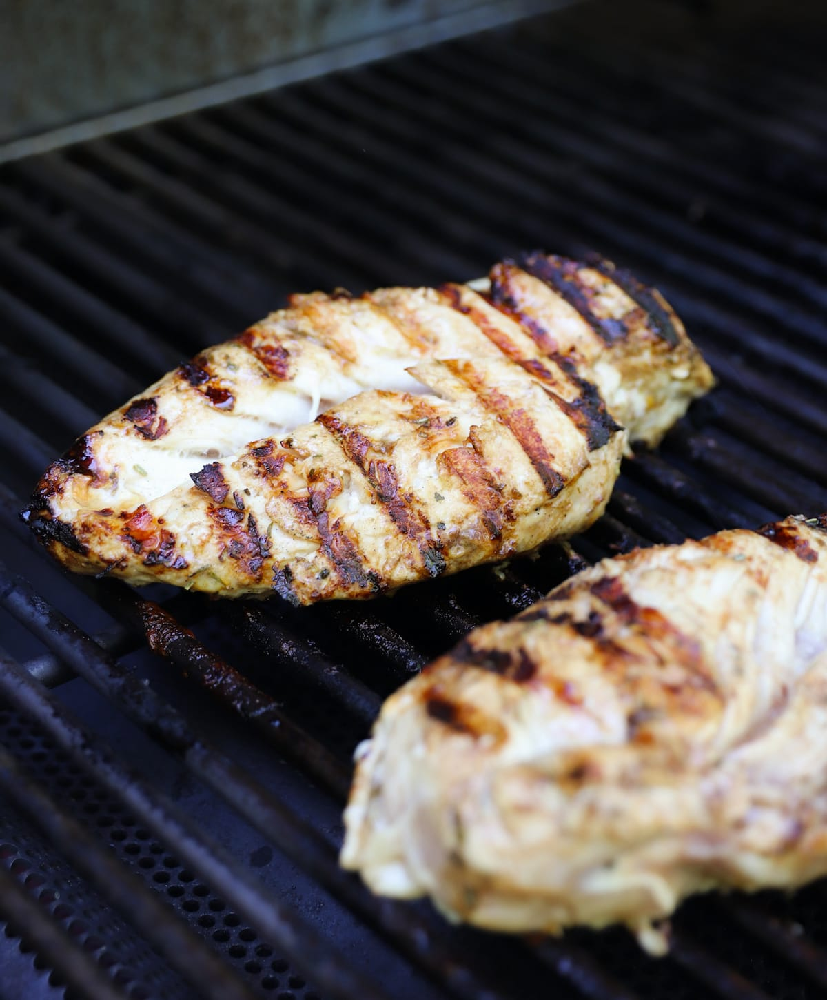 Side view of two chicken breasts cooking on an outdoor grill.
