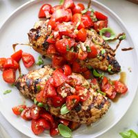 Two plated grilled chicken breasts topped with bright red tomato bruschetta, basil, and vinegar.