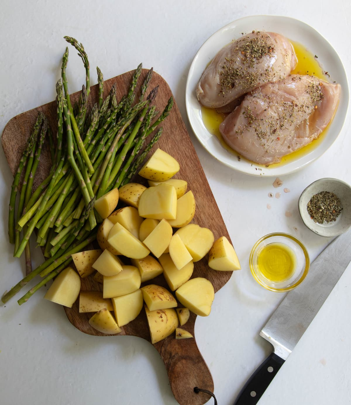 Chicken breasts marinating on a plate beside a cutting board with chopped potatoes and asparagus.