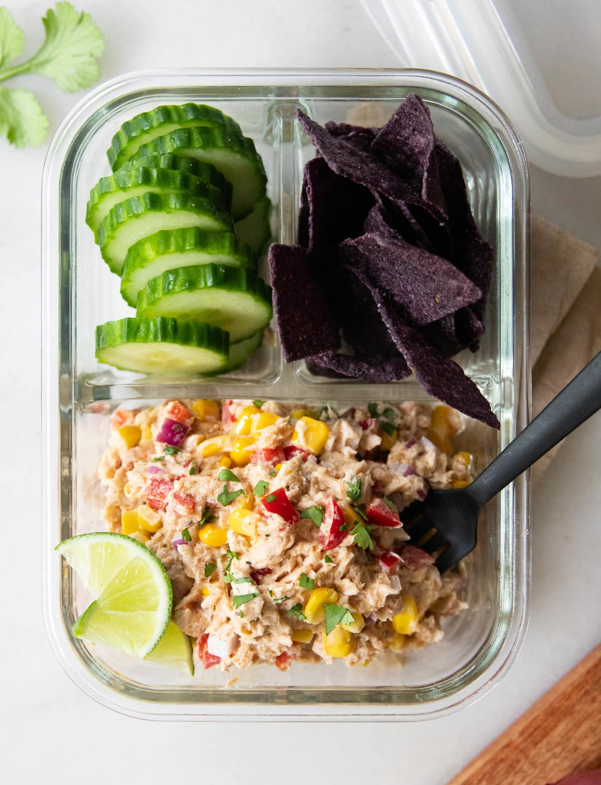 A glass meal prep container filled with Mexican tuna salad, sliced cucumbers, and tortilla chips.