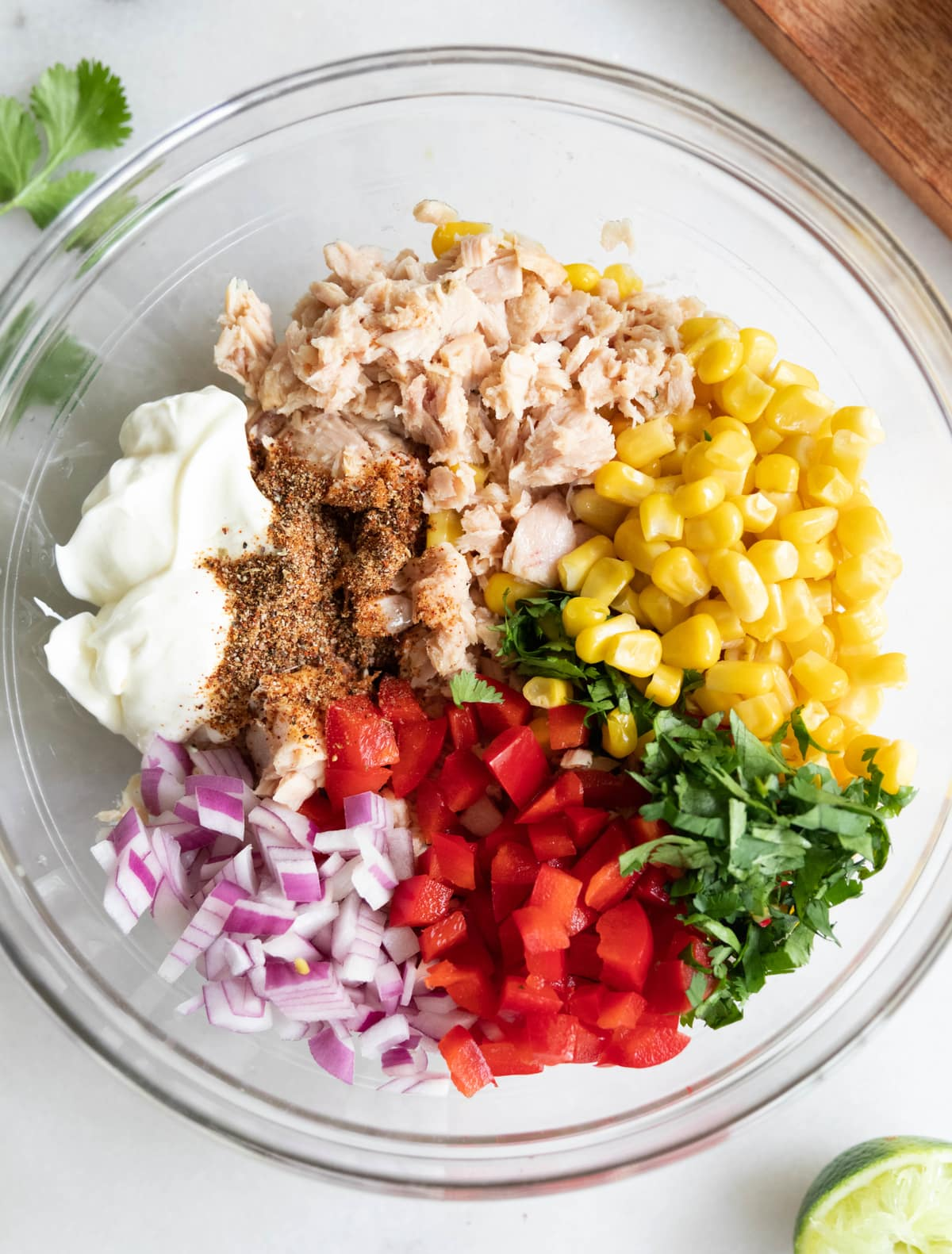 All the tuna salad ingredients added to a large glass bowl, not yet mixed.