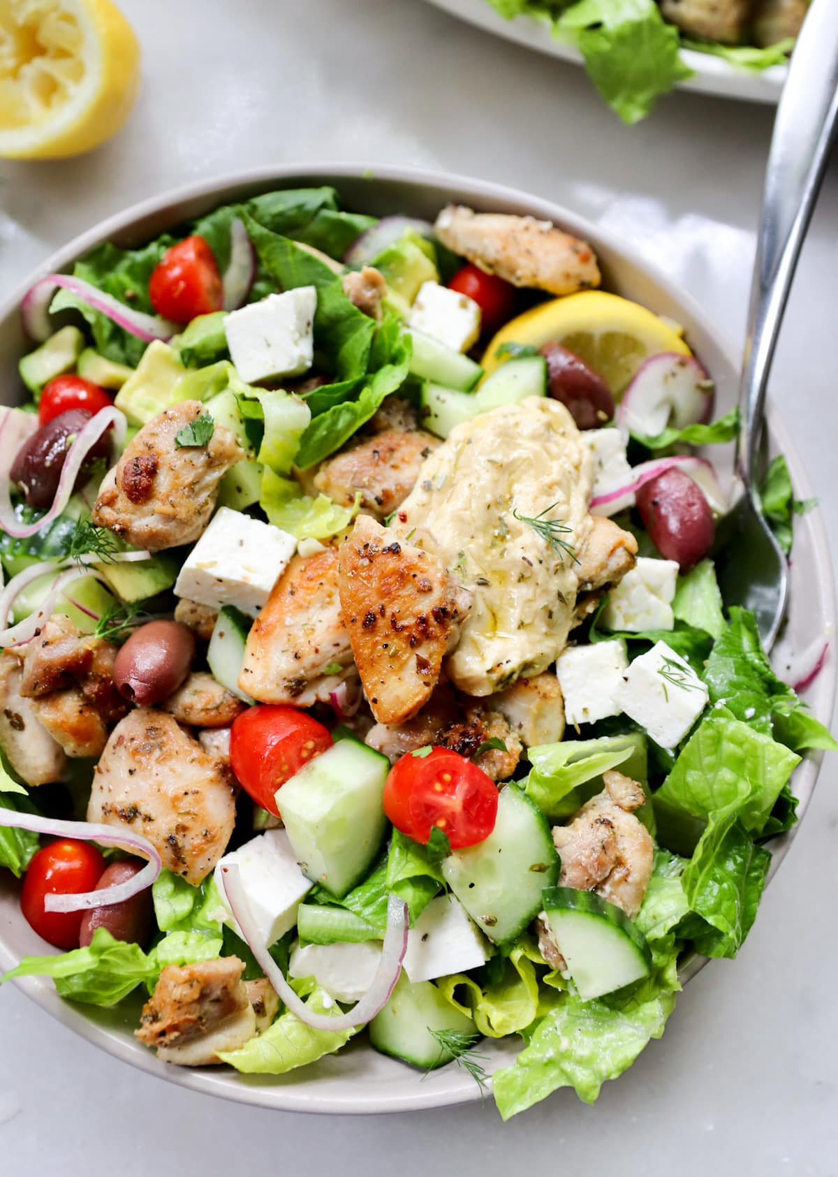 A small bowl filled with the finished salad topped with feta, chicken pieces, and hummus.