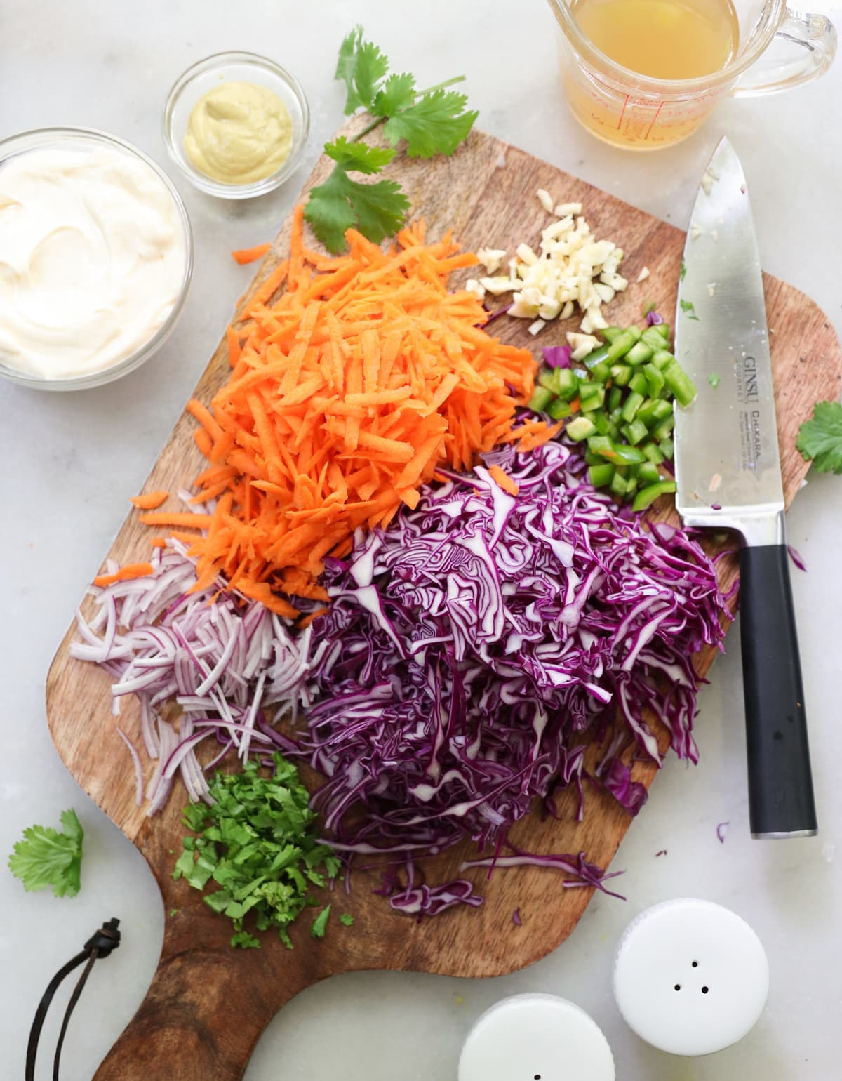 A large wooden cutting board topped with shredded cabbage, carrots, red onion, and minced cilantro, jalapeno, and garlic.