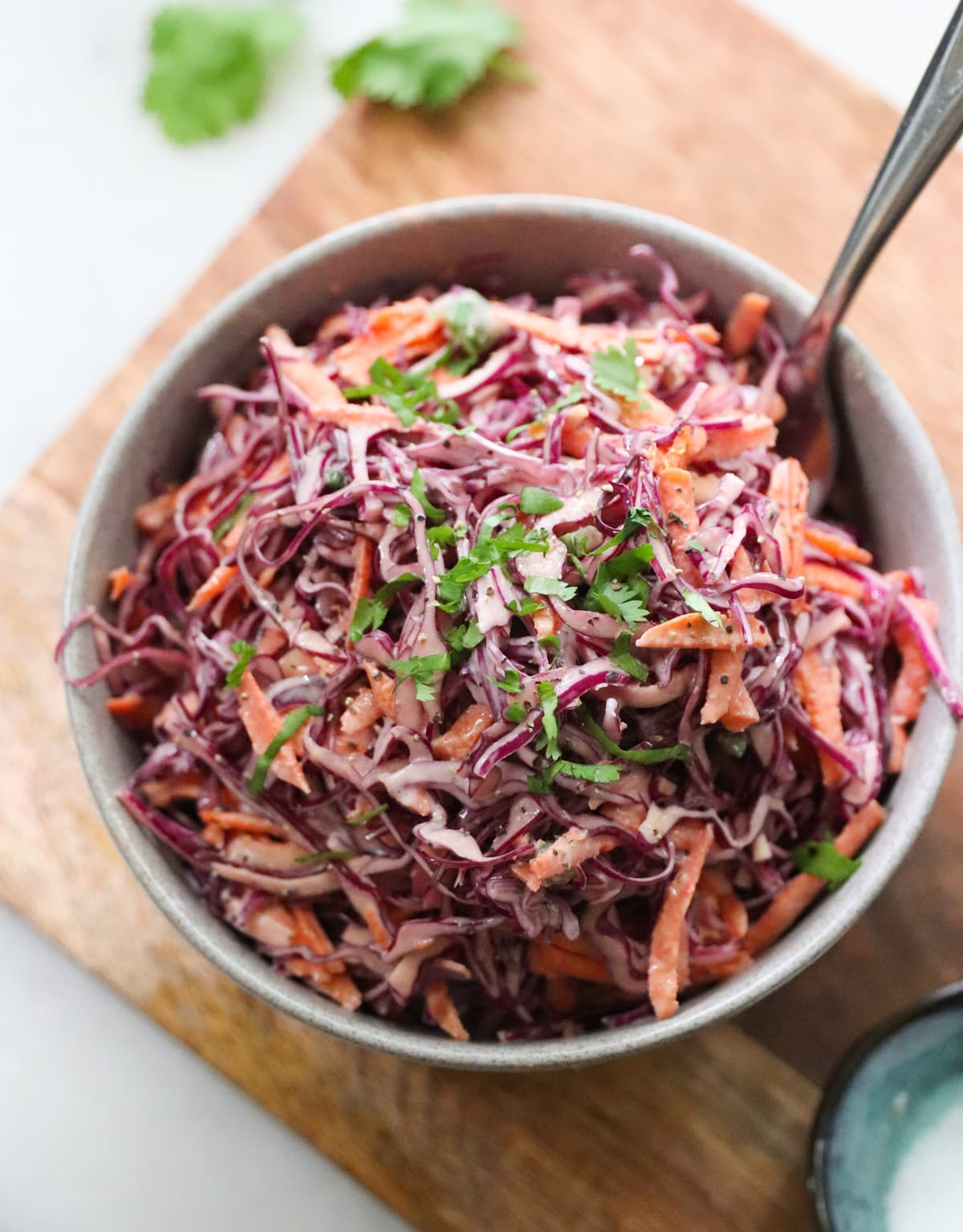 The finished cabbage and carrot cole slaw plated in a gray bowl, garnished with minced cilantro.