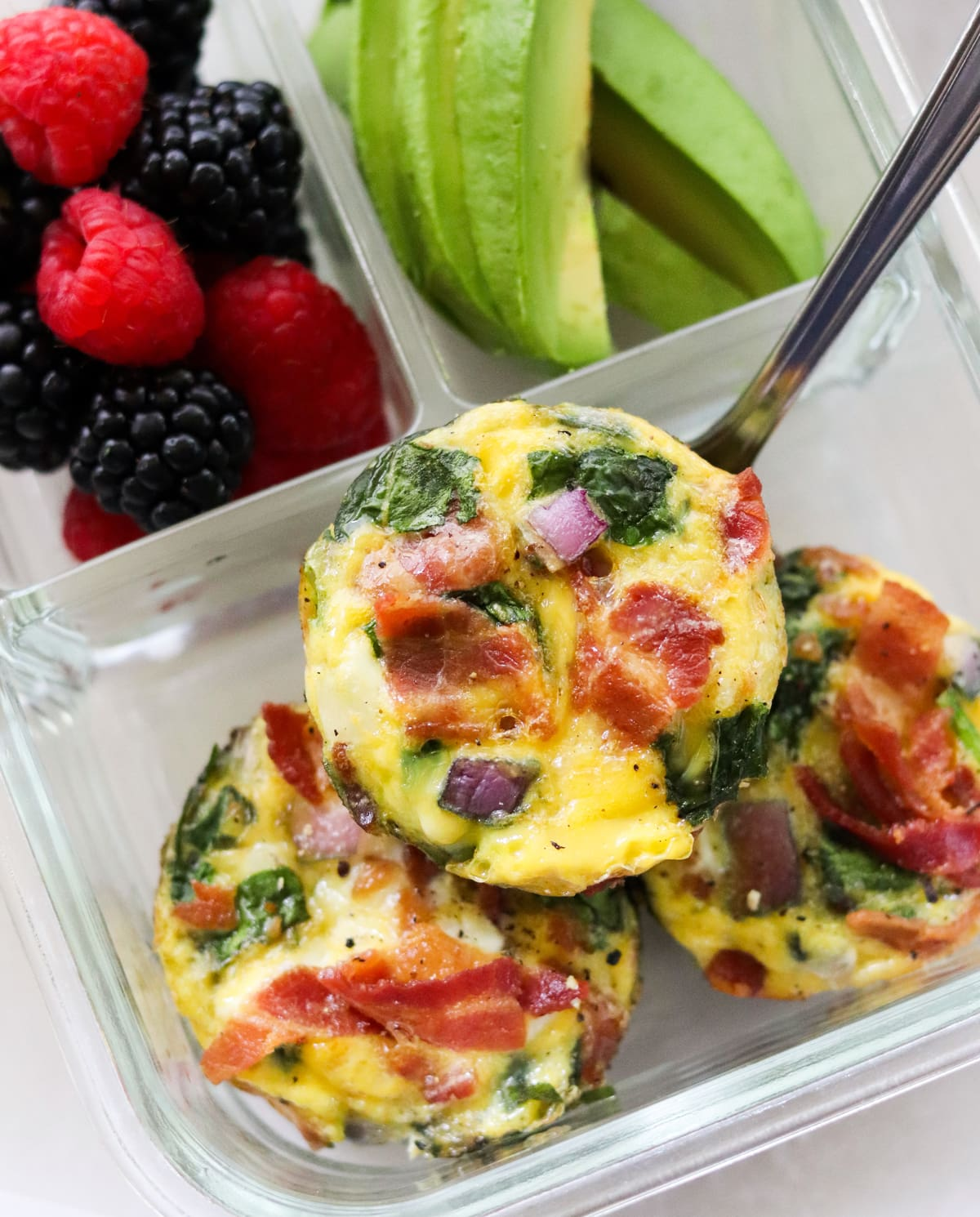 Close up of three bacon and spinach egg muffins in a glass meal prep container with berries and avocado.