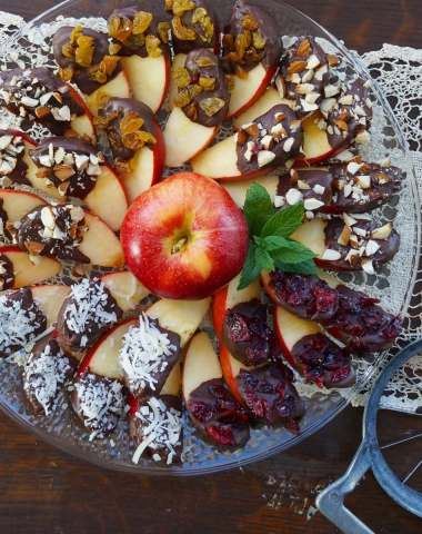 A clear glass plate with layers of slices apples dipped in chocolate and toppings, surrounding one whole apple in the middle.