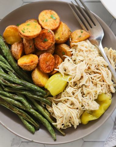 A gray plate filled with Mississippi shredded chicken, potatoes, and green beans.