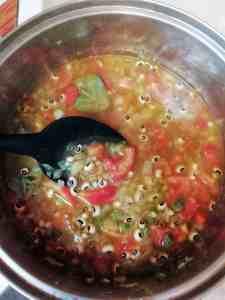 Black peas and broth are added to sautéed vegetables.