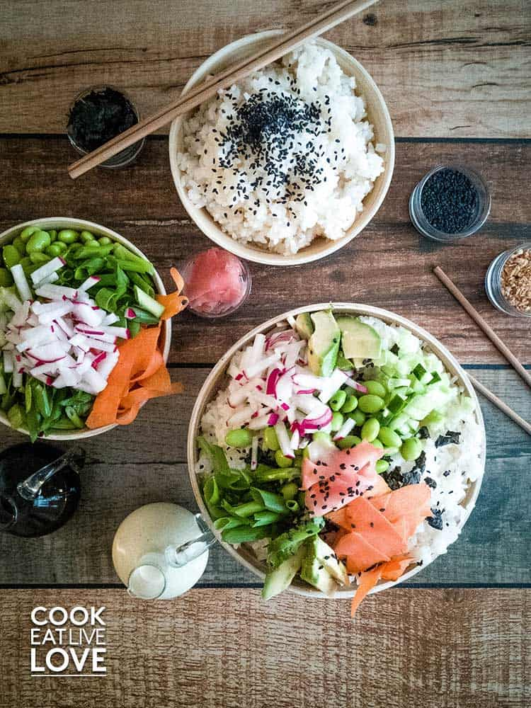 Overhead showing sushi rice bowl with healthy veggies on top.