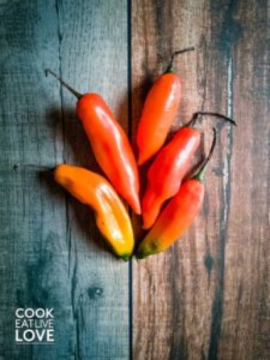 Aji amarillo peppers fresh and whole are shown to demonstrate their bright orange color.