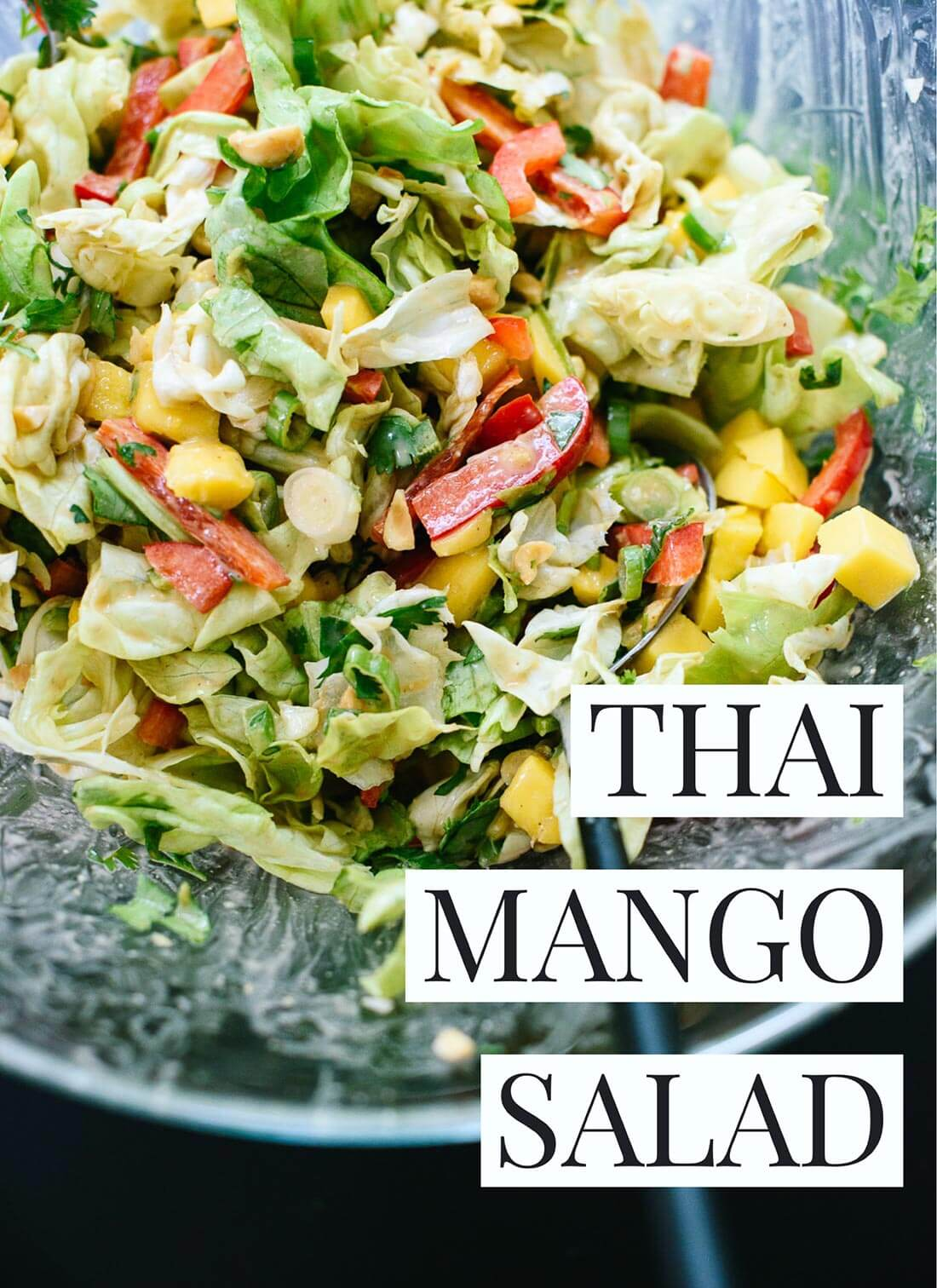 This fresh Thai-flavored salad features mango, bell pepper, greens and a delicious peanut dressing! cookieandkate.com