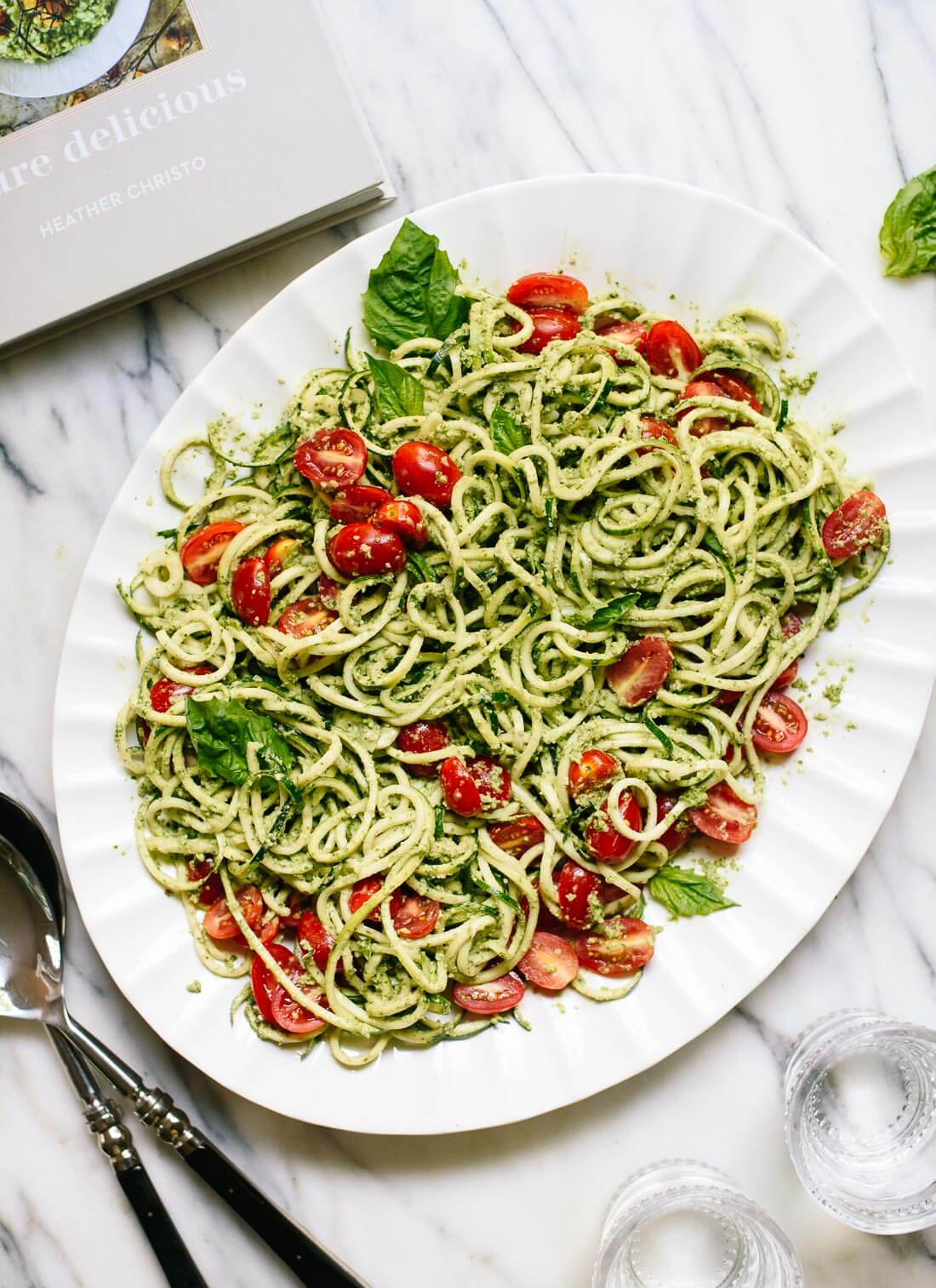 Fresh zucchini noodles with basil pesto and cherry tomatoes makes a light and healthy summer meal! cookieandkate.com
