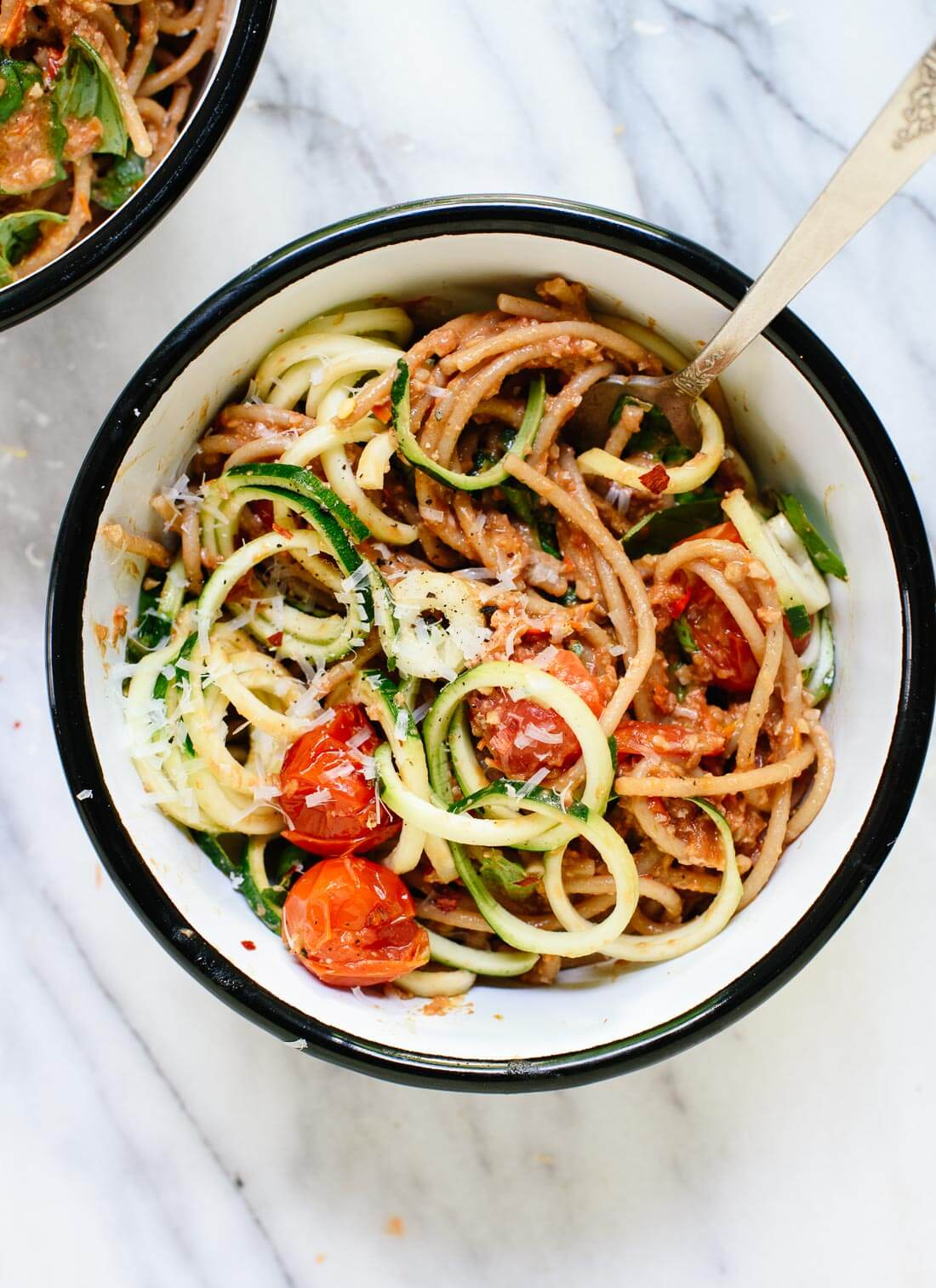 This fresh summer recipe features burst cherry tomatoes, cherry tomato and sun-dried tomato pesto, zucchini noodles, and spaghetti! It's light and delicious. cookieandkate.com