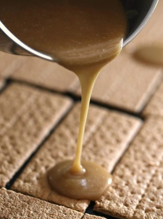 Pouring the butterscotch/caramel sauce over top graham crackers for praline crack!