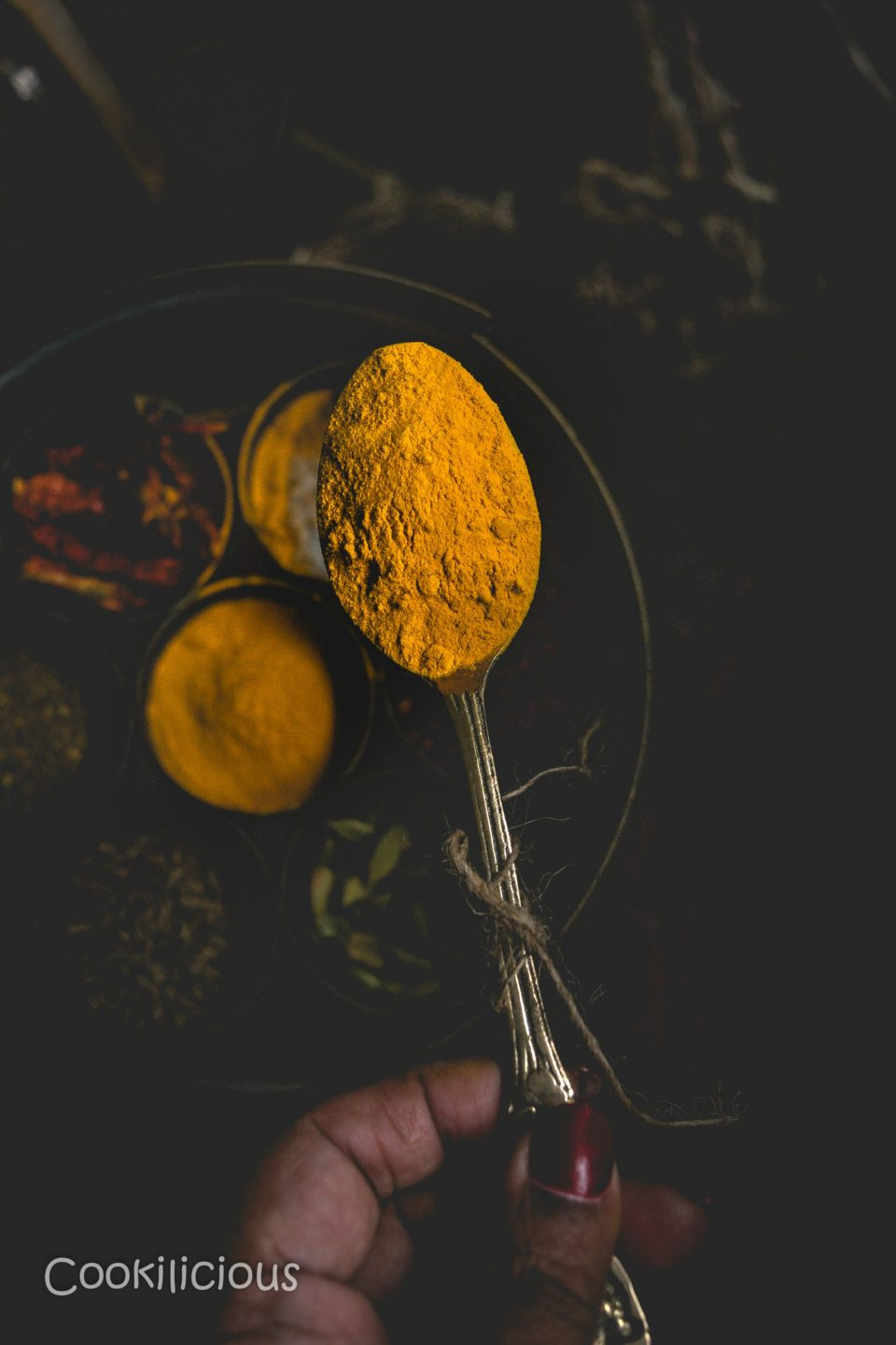 close up shot of a spoonful of turmeric powder