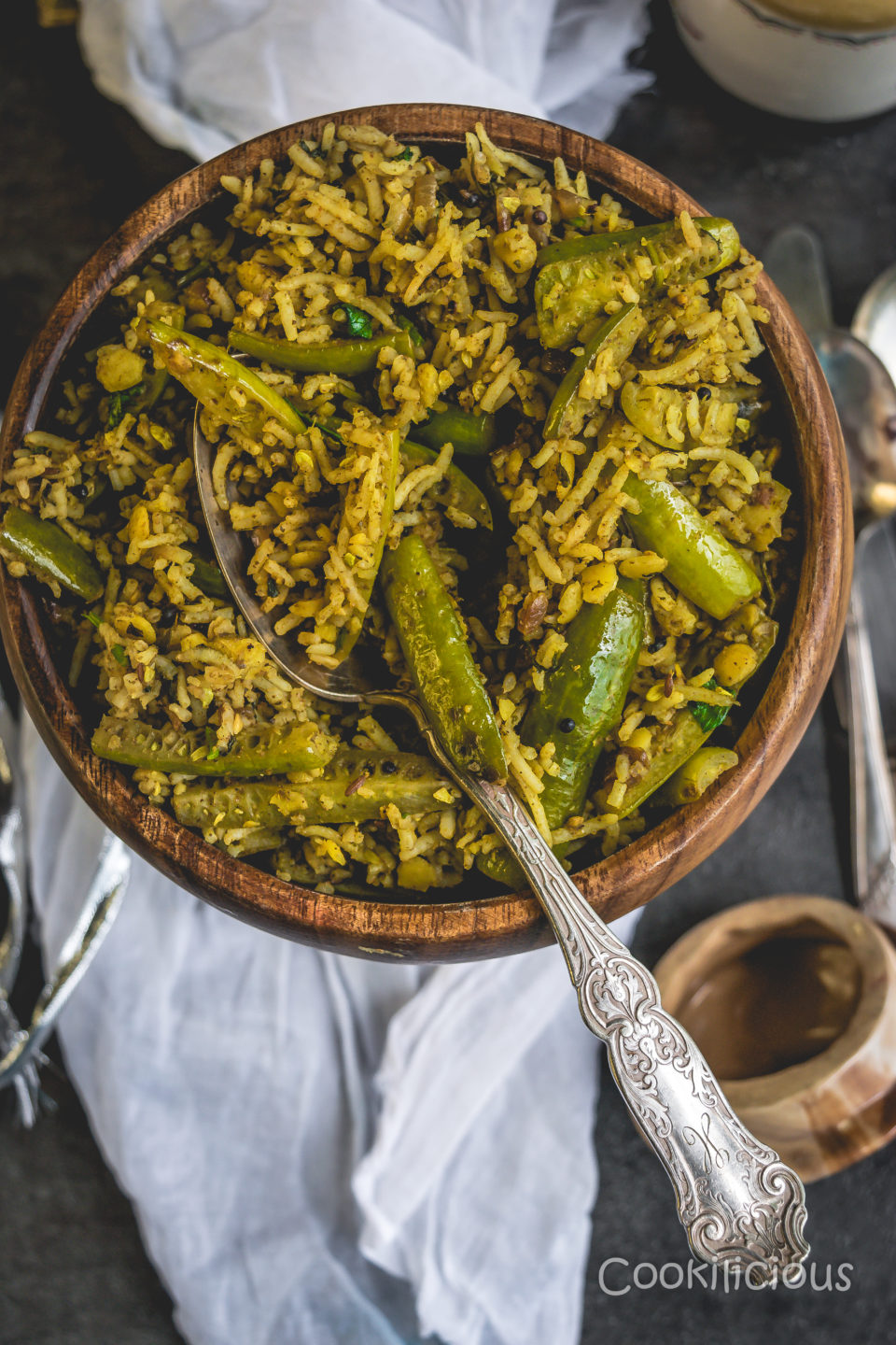 A spoon in a wooden bowl filled with Tendli Masala Bhaat | Ivy Gourd Masala Rice