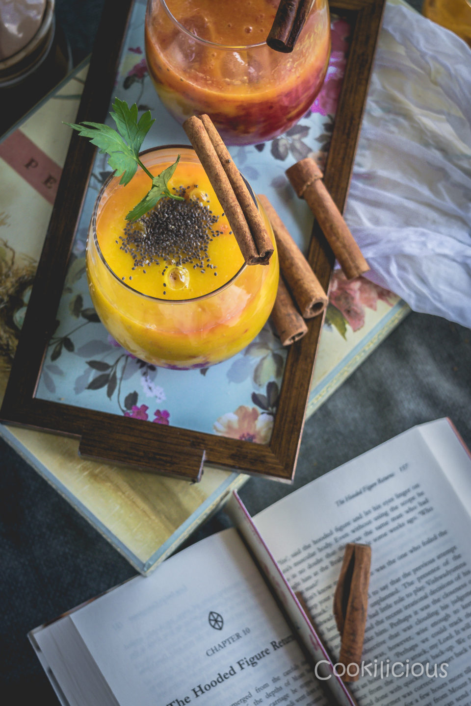 flat lay shot of Fresh Mango Orange Summer Mocktail on a tray with an open book in the background