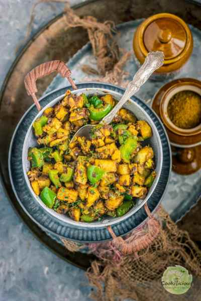 Achari Aloo Capsicum in a kadai with a spoon in it