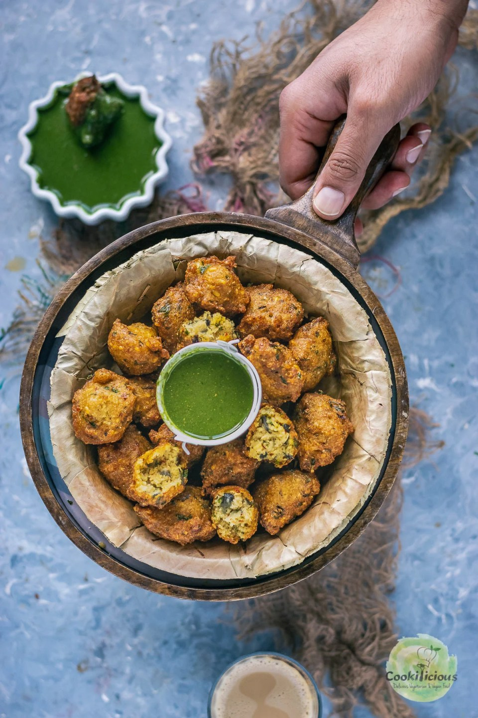 a hand holding a serving platter which has a bowl of Crispy Moong Dal Pakora (one of the popular easy vegan appetizers) and a bowl of green chutney next to it.
