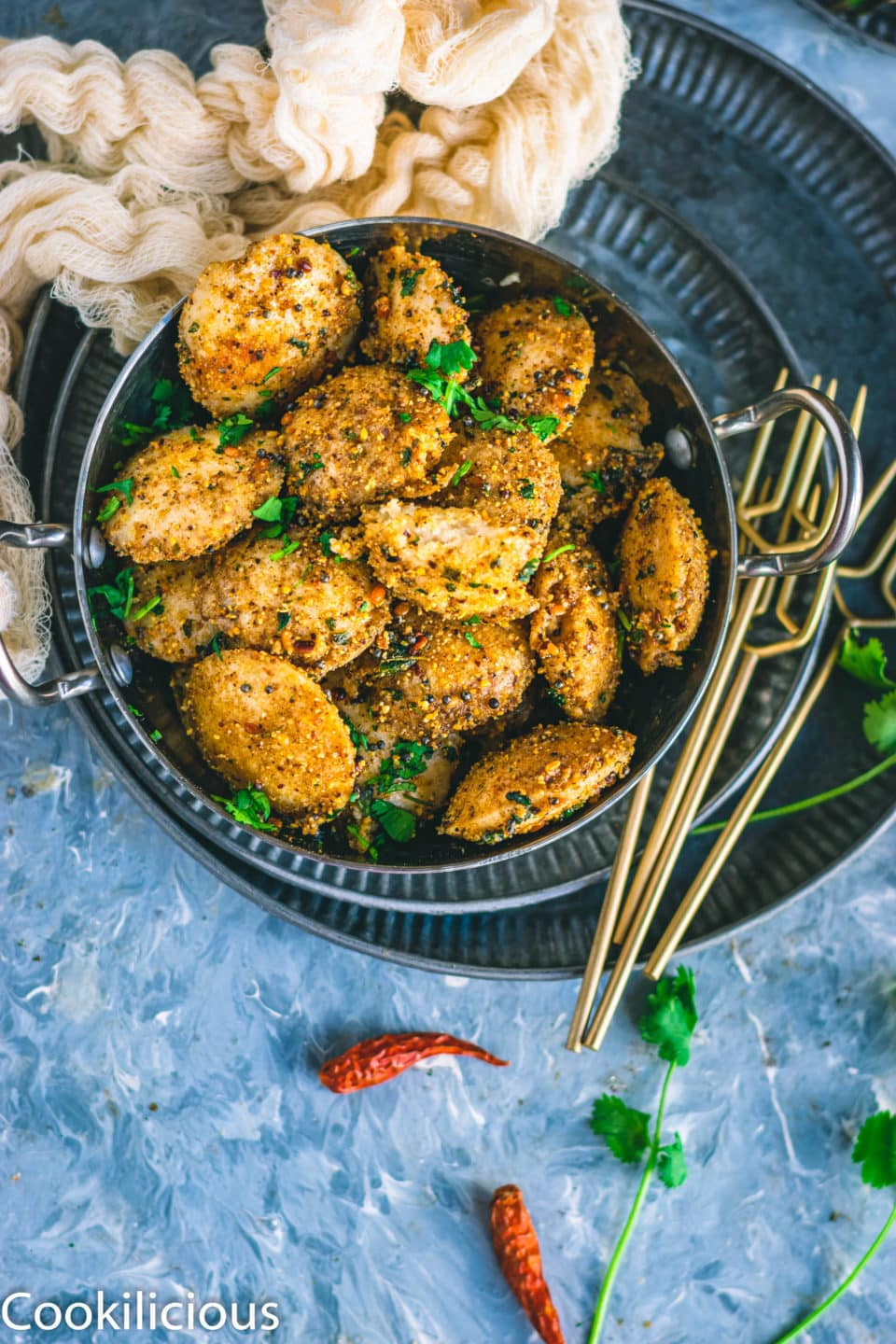 top angle shot of Mini Masala Idli in a small bowl with 4 forks on the side