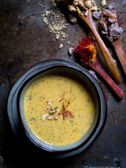 image of Vegan Zaffrani Mewa Doodh in a bowl with spices on the wooden spoons in the background