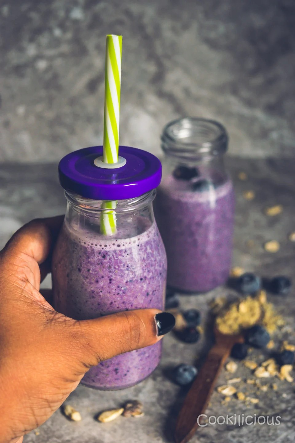 a hand holding a glass of Dairy-Free Blueberry Pancake Smoothie