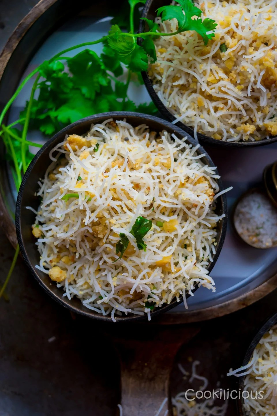 top shot of Lentil & Rice Noodles | Paruppu Sevai in a bowl placed in a round tray with cilantro sprigs in the background.