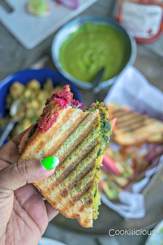 a hand holding a slice of Bombay Style Veg Masala Toast Sandwich