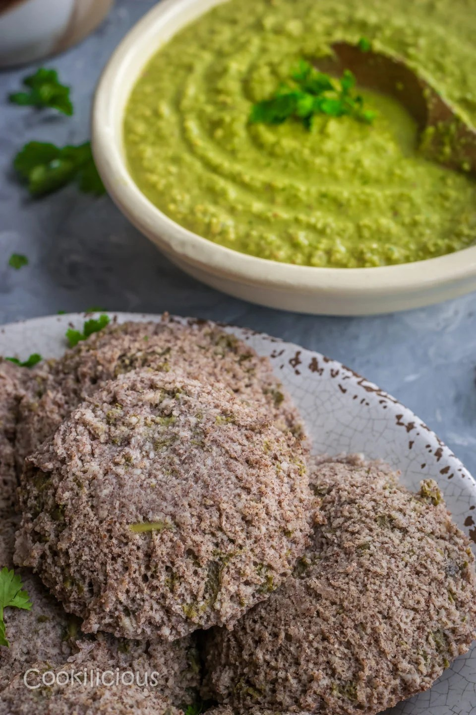 close up to one Ragi & Kale Idli in a plate among others