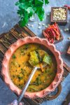 A ladle with veggies dunk into the pot filled with arachuvitta sambhar