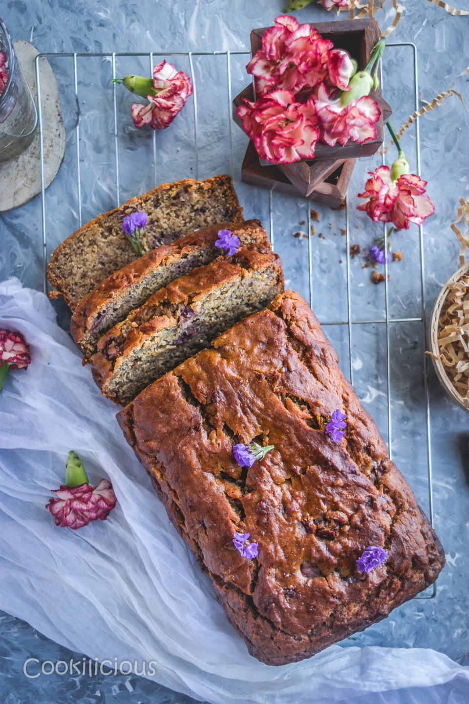 flat lay image of Banana & Strawberry Bread where half of it is cut in slices and flowers around it