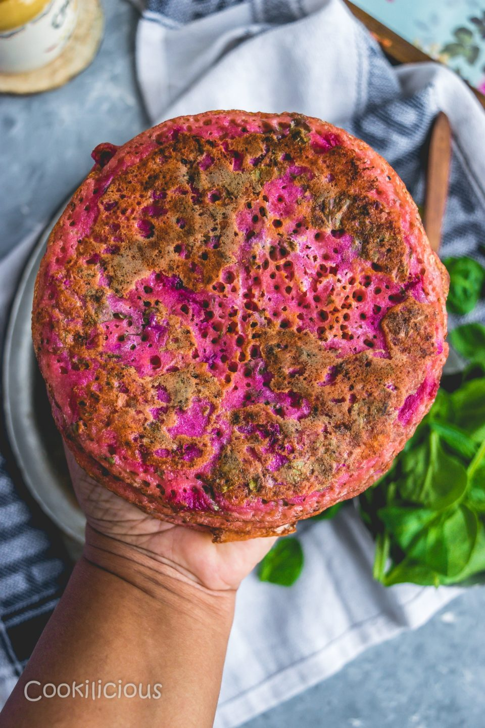 close up shot of a hand holding a Pink Uttapam with Beets & Veggies