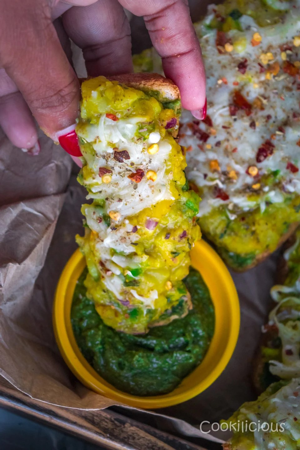 A hand holding a slice of Potato Chilly Garlic Masala Toast and dipping it in green chutney
