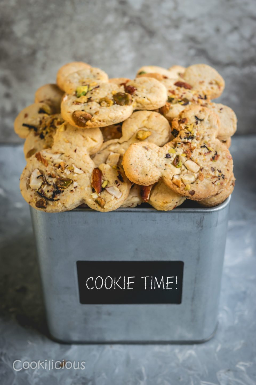 a tin box filled with Eggless Kesar Pista Badam Biscuits/Saffron Cashew Almond Cookies