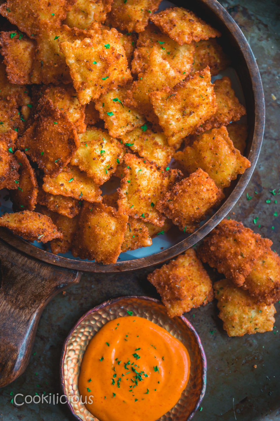 Copycat Olive Garden Cheesy Fried Ravioli in a tray with a dip on the side