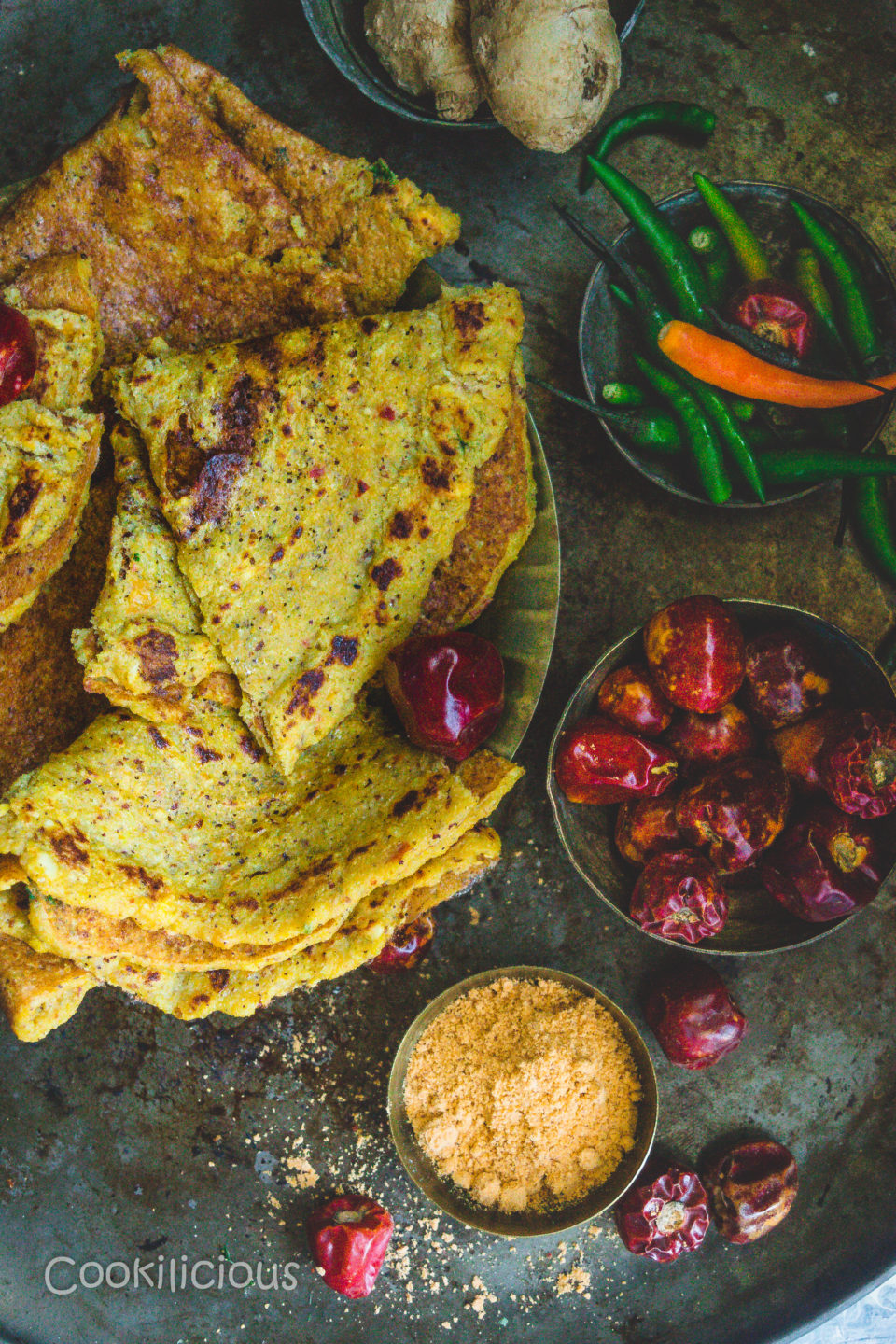 a bowl of mulagapudi, dried red chillies besides a plate filled with Spicy Quinoa & Red Pumpkin Adai