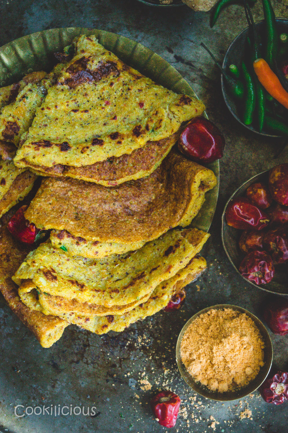 3 Spicy Quinoa & Red Pumpkin Adai neatly stacked one above the other with a bowl of mulagapudi on the side