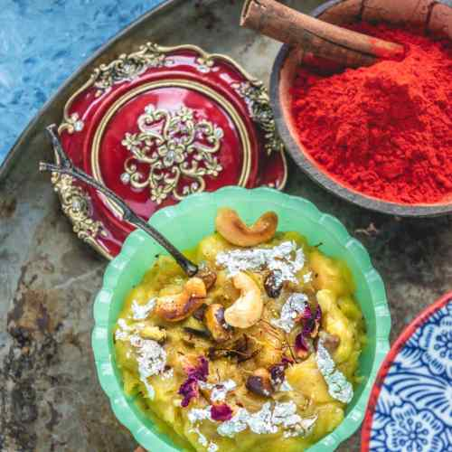 a bowl of Holi color resting next to a bowl of Potato & Sweet Potato Halwa