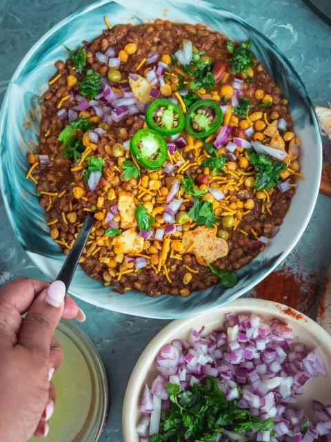 a handing holding a spoon and digging into a bowl of Vegan Matki Misal