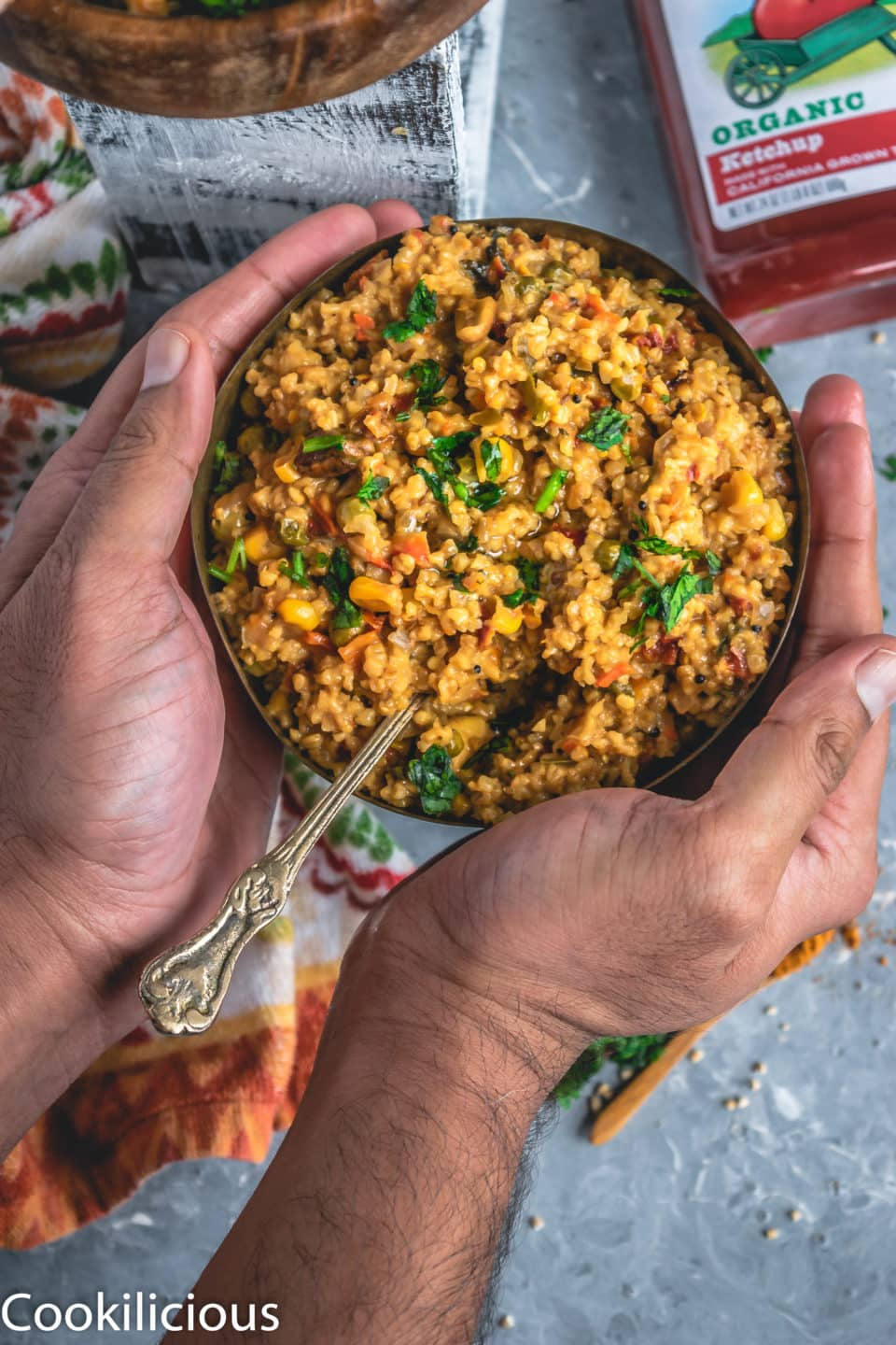 a set of hands wrapped around a bowl of Instant Pot Oats & Vegetable Upma