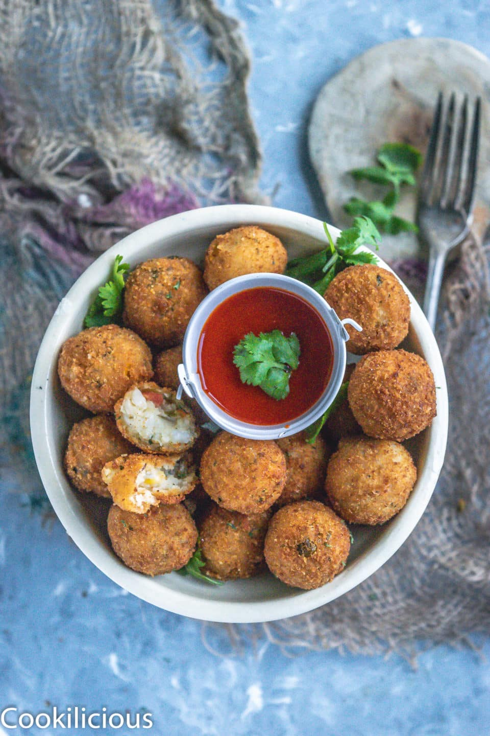 Semolina Vegetable Bites in a plate with a bowl of ketchup in the middle