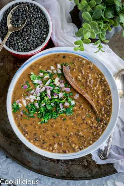 a bowl filled with Black Lentils Stew | Kali Dal | Maa Ki Daal and black lentils in a bowl on the side