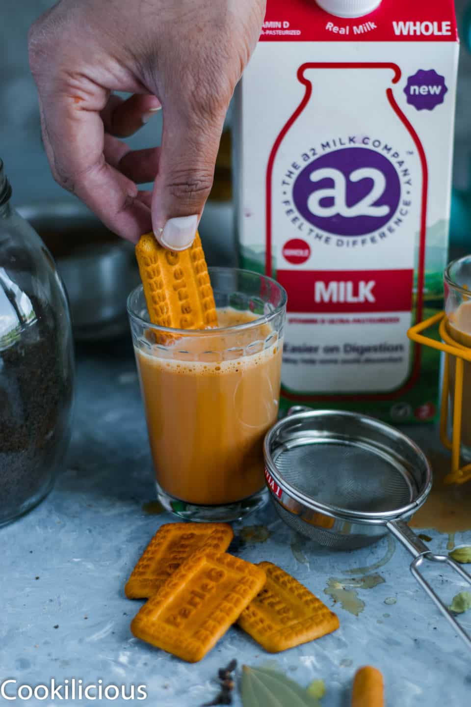 a hand dipping a biscuit into a glass of masala chai with a2 milk in the background