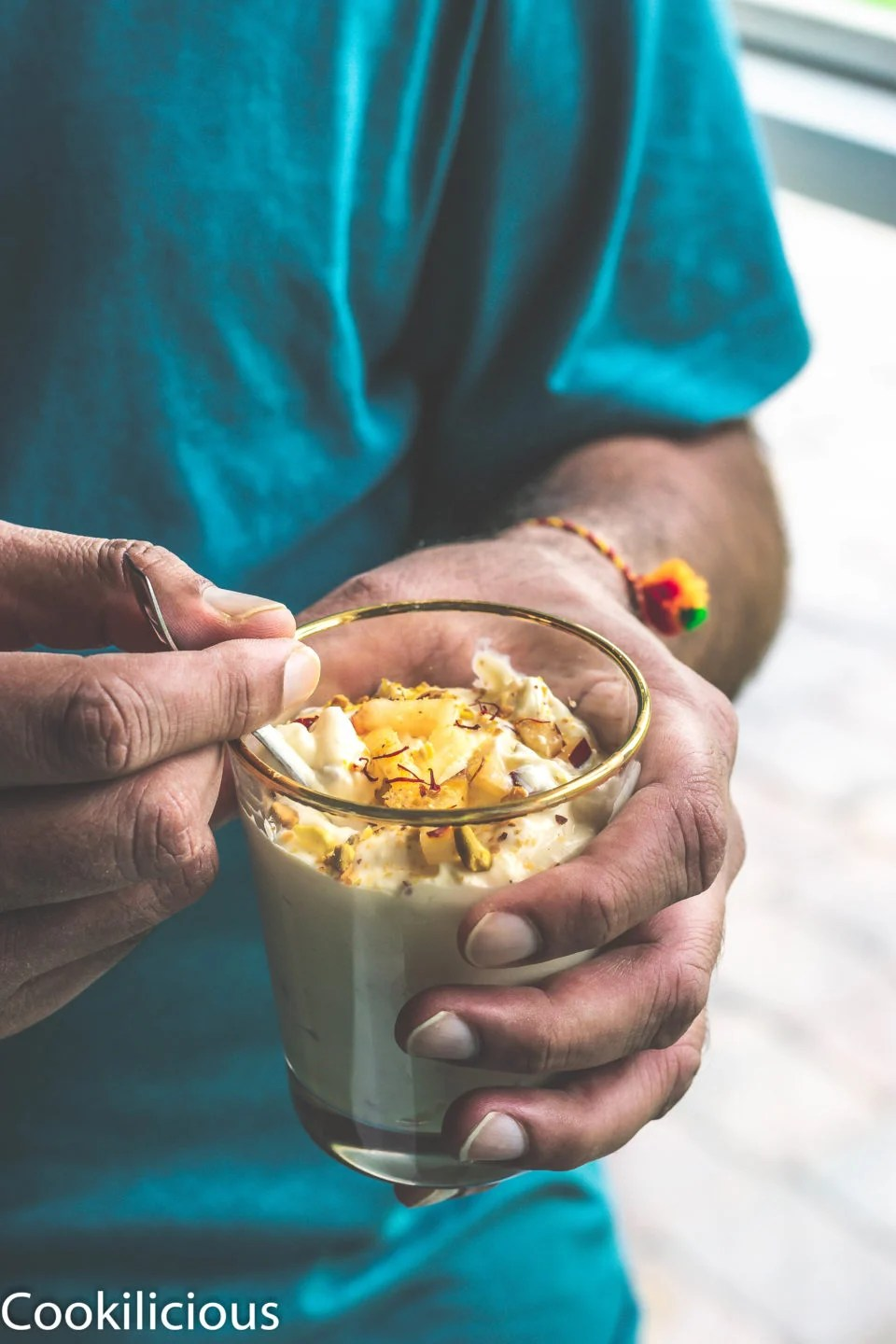 a man holding a glass filled with Apple & Pistachio Mousse