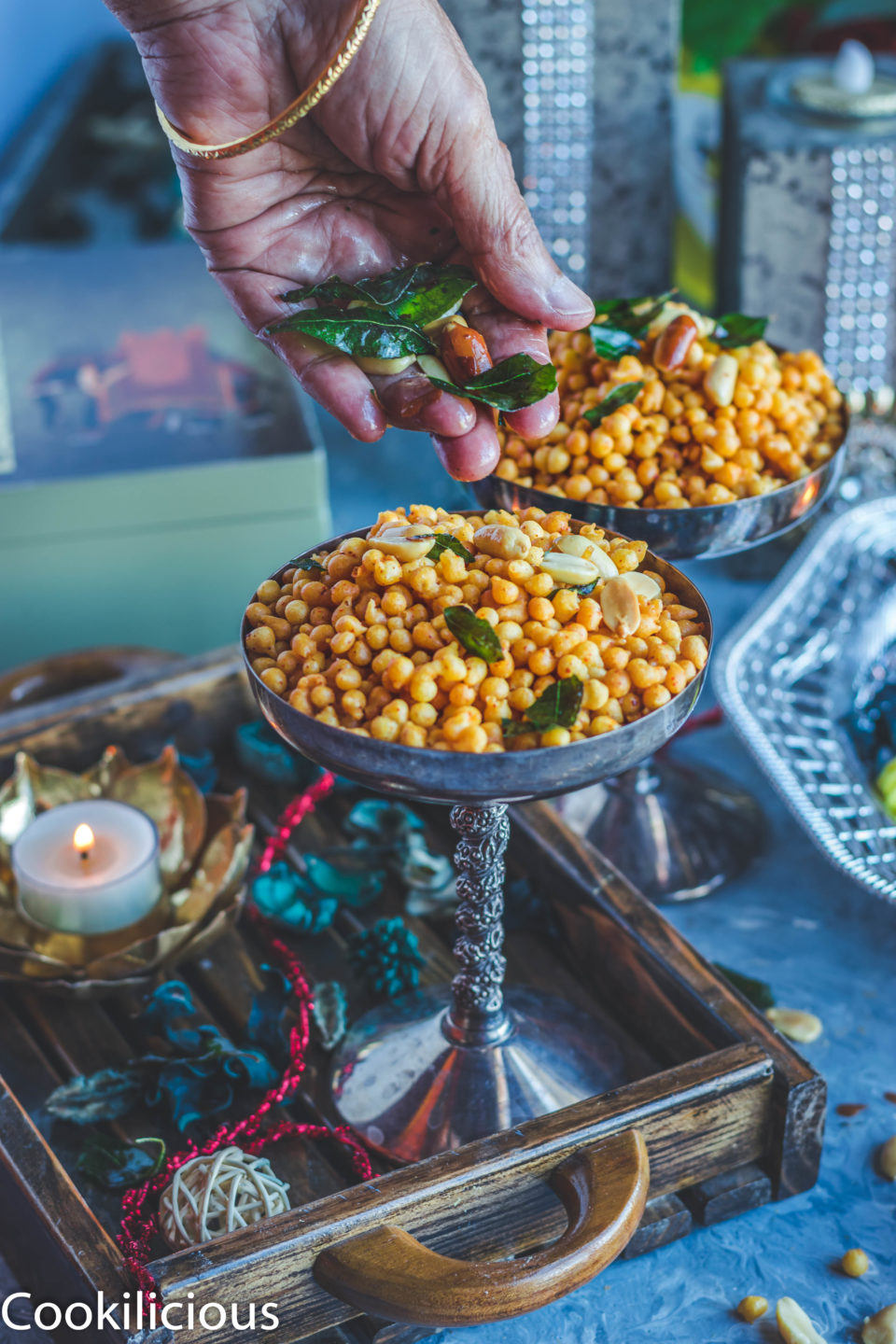 a hand garnishing a glass full of Kara Boondi Mixture with fried curry leaves