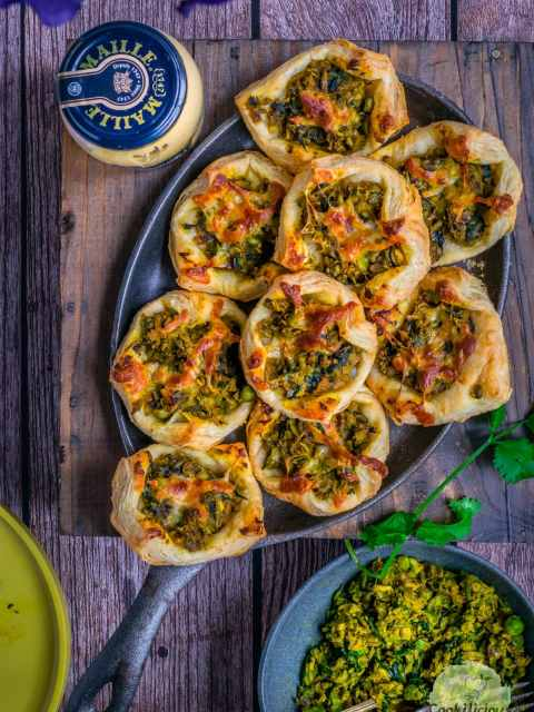 flat lay image of Spicy Green Peas & Spinach Pastry Puffs in a tray with a jar of Maille Mustard on the side and some leftover filling on the other side