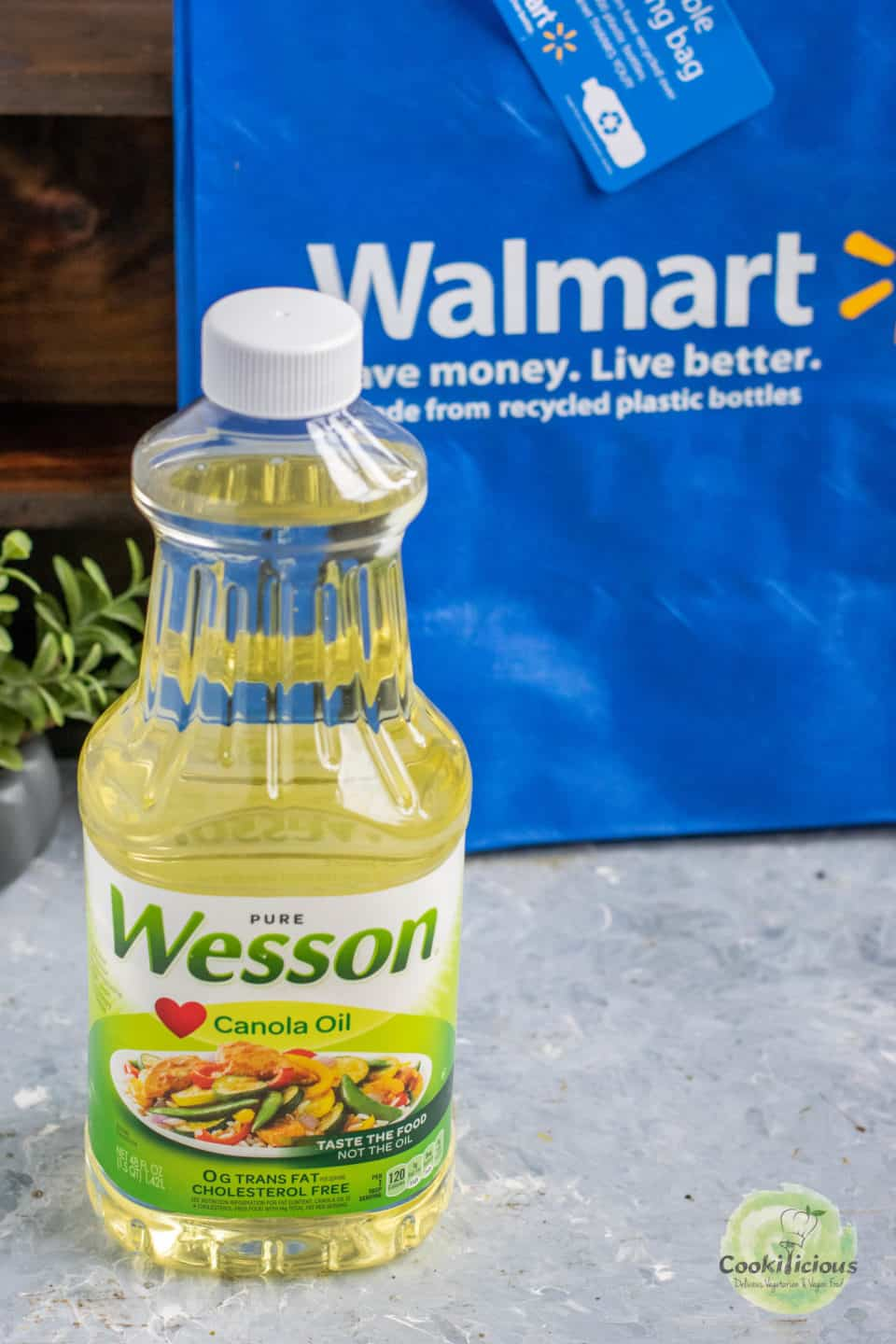 image of Wesson Canola Oil in a bottle with a Walmart bag behind it