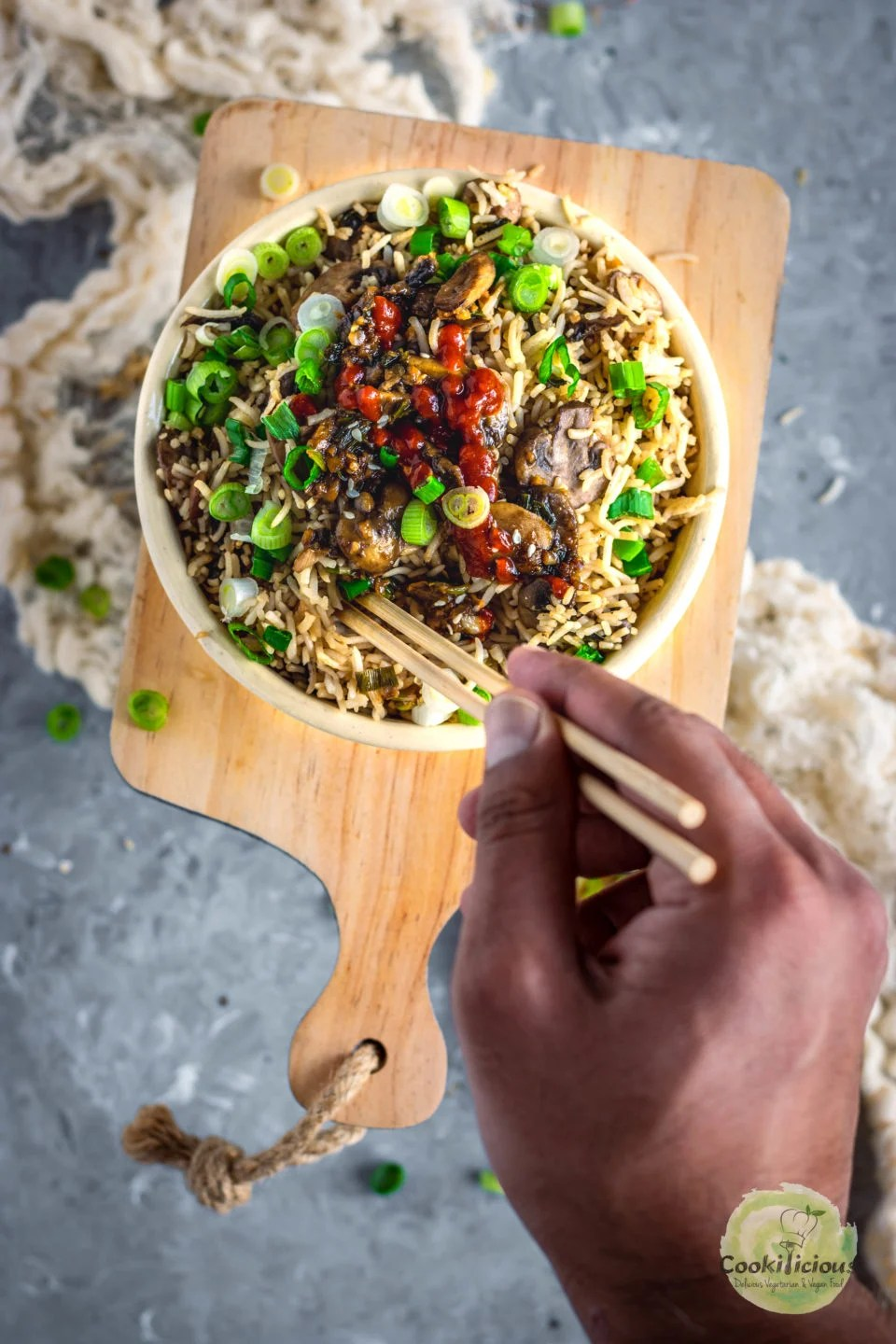 a hand holding chopsticks digging into a Japanese fried rice bowl