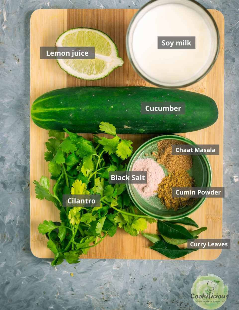 all ingredients needed to make cucumber chaas is placed over a wooden board